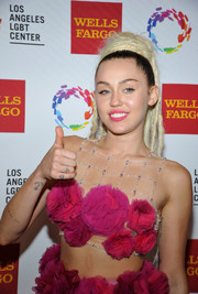Miley Cyrus displayed her alien head tattoo while doing a thumbs up during the Vanguard Awards.