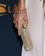 Eva Mendes paired her chiffon dress with a gold clutch.