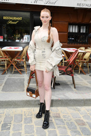 Larsen Thompson flaunted her slim figure in a nude one-shoulder mini dress at the Louis Vuitton Menswear show.