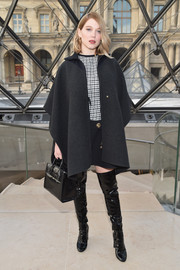 Lea Seydoux layered a black wool cape over a monochrome mini dress for the Louis Vuitton fashion show.