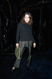 Tallulah Harlech went to the Louis Vuitton fashion show wearing iridescent gray slacks and a matching sweater.