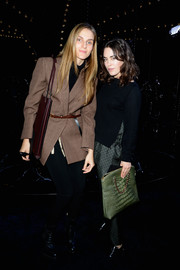 Tallulah Harlech accessorized with an ultra-stylish green crocodile tote at the Louis Vuitton fashion show.