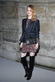 Emma Stone layered a belted blazer over a print dress, both by Louis Vuitton, for the brand's Fall 2018 show.
