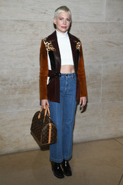 Michelle Williams layered a Louis Vuitton paneled suede jacket over her crop-top for a chicer finish.