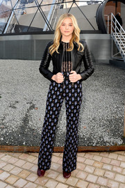 Chloe Grace Moretz layered a black leather jacket over a sheer top for edgy-girly feel during the Louis Vuitton fashion show.