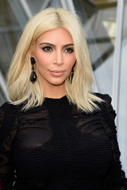 Kim Kardashian attended the Louis Vuitton fashion show wearing edgy center-parted layers.