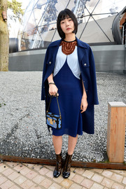 Bae Doo-Na arrived for the Louis Vuitton fashion show wearing a blue wool coat over a tricolor dress.