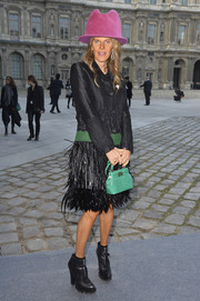 Anna dello Russo accessorized her outfit with an elegant green crocodile purse by Bulgari.