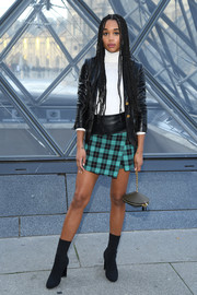 Laura Harrier layered a black leather jacket over a white turtleneck for the Louis Vuitton Fall 2019 show.