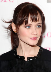 Alexis displays her auburn bangs with a sleek ponytail.