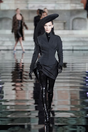 Bella Hadid walked the LuisaViaRoma CR runway wearing a fitted charcoal skirt suit by Mugler.