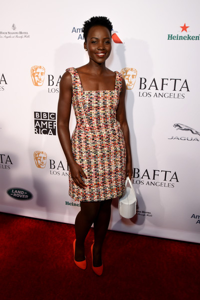 Lupita Nyong'o Pumps [white,clothing,red carpet,dress,carpet,fashion,cocktail dress,shoulder,hairstyle,fashion design,lupita nyongo,tea party,los angeles,four seasons hotel,california,beverly hills,bbca bafta]