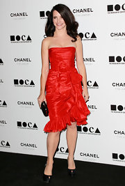 Kristin is on fire in this iridescent red Oscar De La Renta dress.  The strapless number shows off the actresses curves. The bright eye-catching color is perfect for her dark curls and black accessories.