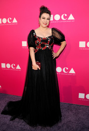 Jennifer Tilly added an extra pop of color with a red hard-case clutch.
