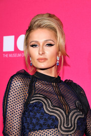 Paris Hilton accessorized with a pair of dangling sapphire and diamond earrings by Cartier.