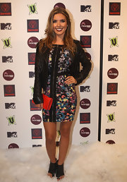 Audrina Patridge toughened her bold floral print mini dress with a pair of futuristic black leather cutout booties. She finished off the look with a red clutch and leather jacket.