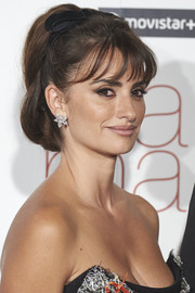 Penelope Cruz paired her hairstyle with lovely diamond flower studs.