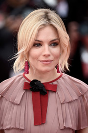 Sienna Miller complemented her 'do with a pair of gemstone chandelier earrings by Bulgari.