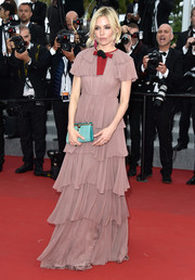 Sienna Miller injected some brightness into her look with an aqua-blue satin clutch by Bulgari.