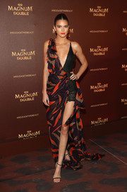 Kendall Jenner flaunted her cleavage and pins in this asymmetrical print gown by Versace during the Magnum Doubles Party.