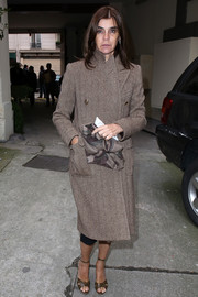 Carine Roitfeld attended the Maison Martin Margiela fashion show wearing brown ankle-strap sandals and a tweed coat.