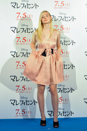Elle Fanning exuded girly charm in a sleeveless pink Lanvin cocktail dress with rosette waist accent during the 'Maleficent' press conference in Tokyo.
