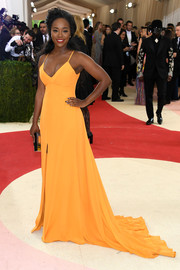 Aja Naomi King flashed some cleavage in a low-cut orange fishtail gown at the Met Gala.