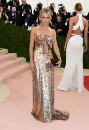 Sienna Miller scintillated in a strapless gold column dress by Gucci at the Met Gala.