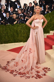 Blake Lively looked magnificent at the Met Gala in a blush-colored Burberry strapless gown with a floral-embroidered cape.