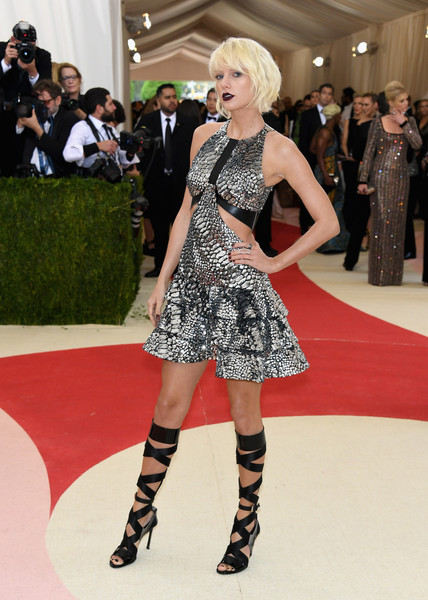 Taylor Swift looked super sassy at the Met Gala in a silver Louis Vuitton cutout dress rendered in python-patterned sequins.
