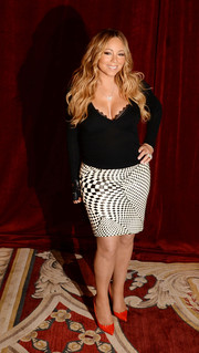 Mariah Carey paired her sweater with a short pencil skirt featuring a warped checker print.