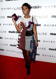 Janelle Monae rounded out her busy-looking ensemble with a purple box clutch by Edie Parker.