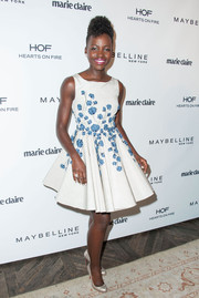 A pair of iridescent Christian Louboutin round-toe pumps sealed off Lupita Nyong'o's charming look.