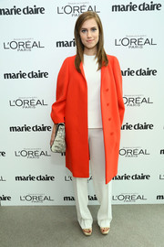Allison Williams perked up her all-white blouse and slacks combo with an orange Calvin Klein coat when she attended the Marie Claire Power Women Lunch.