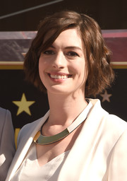 Anne Hathaway went for modern styling with a gold and white collar necklace by Marni.