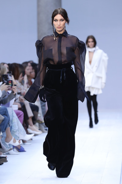 Bella Hadid flashed some skin in a sheer black blouse while walking the Max Mara runway.