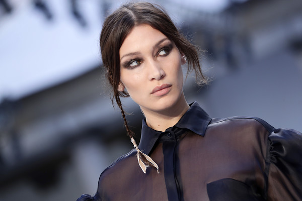Bella Hadid wore a loose center-parted ponytail with a thin braid hanging down one side at the Max Mara runway show.