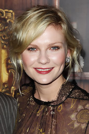 Kirsten Dunst wore her hair in a super simple bun at the UK premiere of 'Melancholia'. To recreate her low-key look, section out some hair around the face and loosely pull the rest back into a low ponytail.  Twist the ponytail and wrap it around the hair elastic, then secure it in place with a few bobby pins.