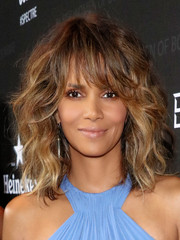 Halle Berry rocked voluminous curls with eye-grazing bangs at the Black Women of Bond Tribute.