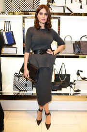 Catrinel Marlon stuck to a neutral palette, accessorizing her gray outfit with a black leather clutch.