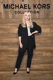 Dove Cameron opted for an oversized black pinstriped pantsuit when she attended the Michael Kors Fall 2020 show.