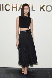 Tao Okamoto put her super-slim physique on show in a tight black crop-top by Michael Kors during the label's fashion show.