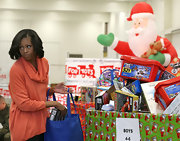 Michelle Obama looked stylish in an orange cowl-neck top while distributing toys and gifts.