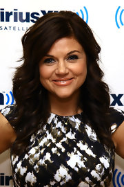 Tiffani Theissen visited SiriusXM Studios wearing her long hair in feathered waves with side-swept bangs.