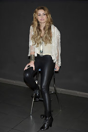 Miley toughens up her lace blouse with some leather leggings and lace up lather boots.
