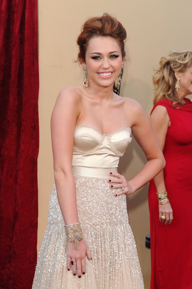 Miley Cyrus Red Nail Polish [dress,hair,clothing,gown,red carpet,carpet,lady,flooring,shoulder,hairstyle,arrivals,miley cyrus,singer,hollywood,california,kodak theatre,82nd annual academy awards]