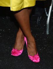 Tika Sumpter went for bold colors at the Milly by Michelle Smith fashion show, pairing pink satin evening pumps with her yellow dress.