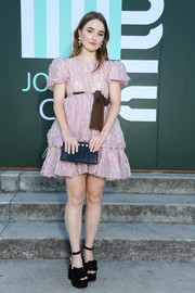 Kaitlyn Dever teamed her frock with a pair of chunky, rosette-adorned platforms by Miu Miu.