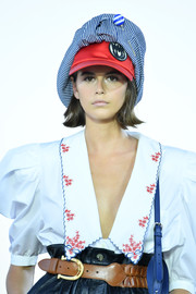 Kaia Gerber accessorized with a funky newsboy cap on the Miu Miu Club 2020 runway.