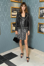 Alexa Chung toughened up her frock with a studded black leather jacket.